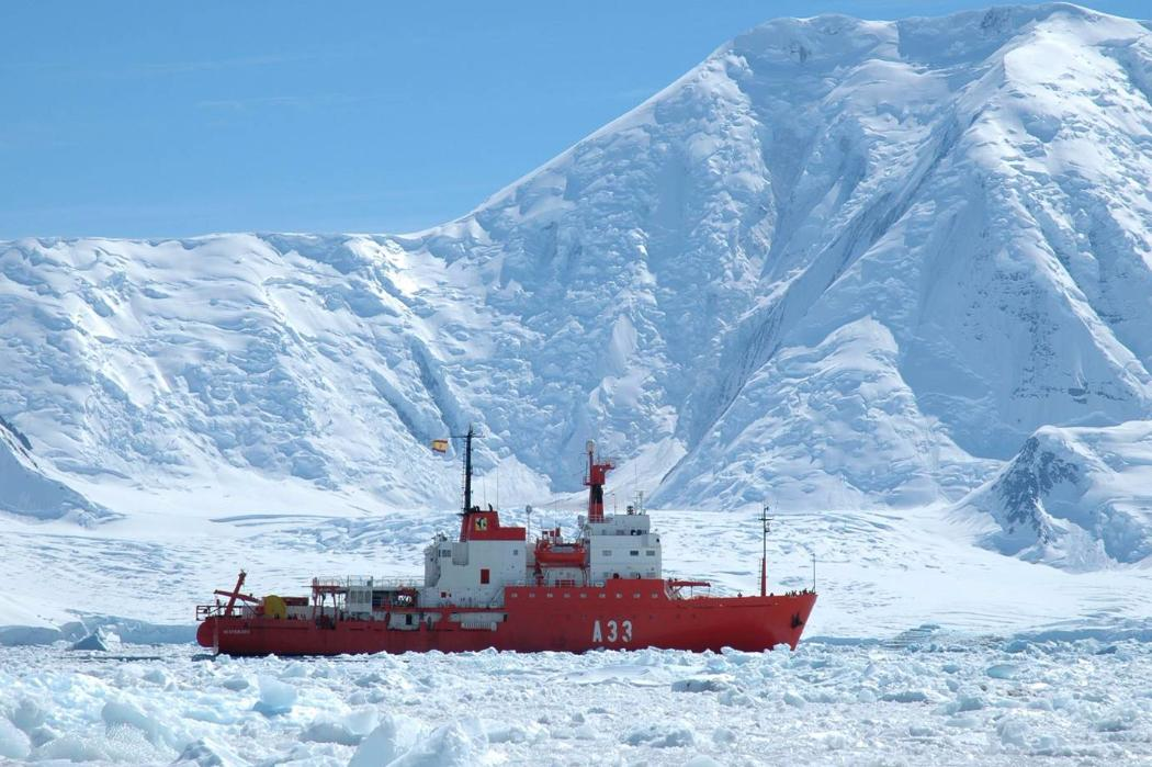 ship cutting through ice floes in antarctica