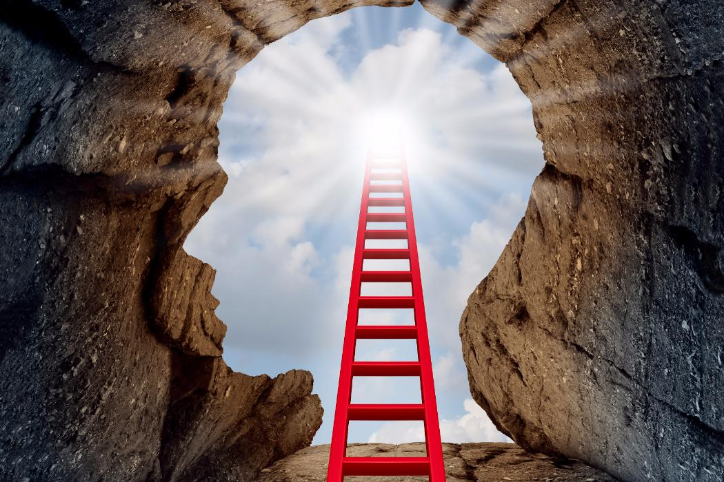 Red ladder ascending out of head shaped hole