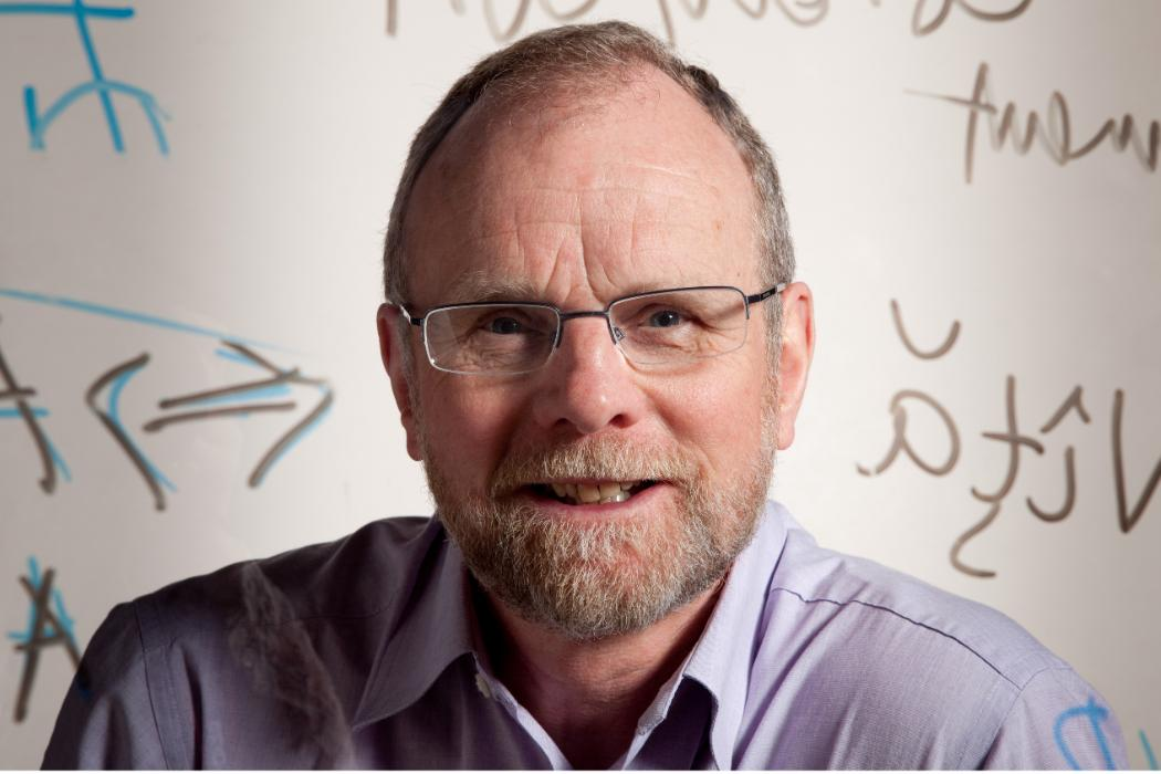 Professor Douglas Bridges behind mathematical equations on clear board