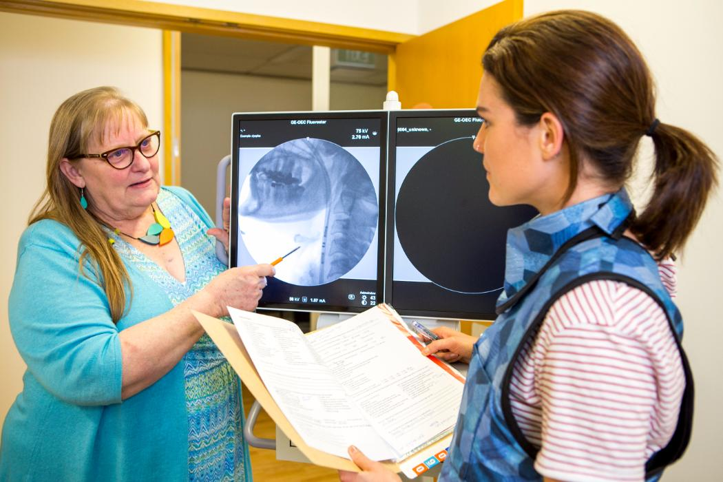 Researcher and postgrad looking at scan of throat on a screen