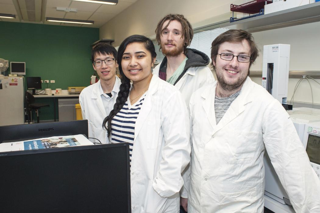 four biology students in lab wearing white coats