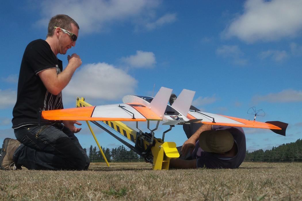 Two men launchoing aeroplane drone