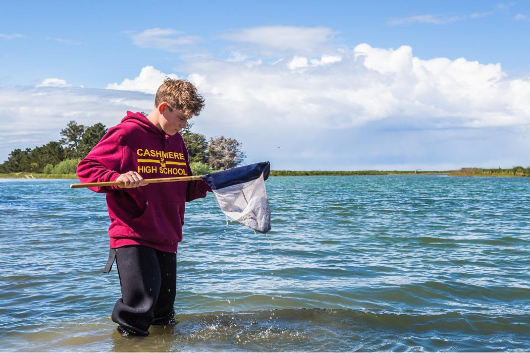 science outreach student in waders