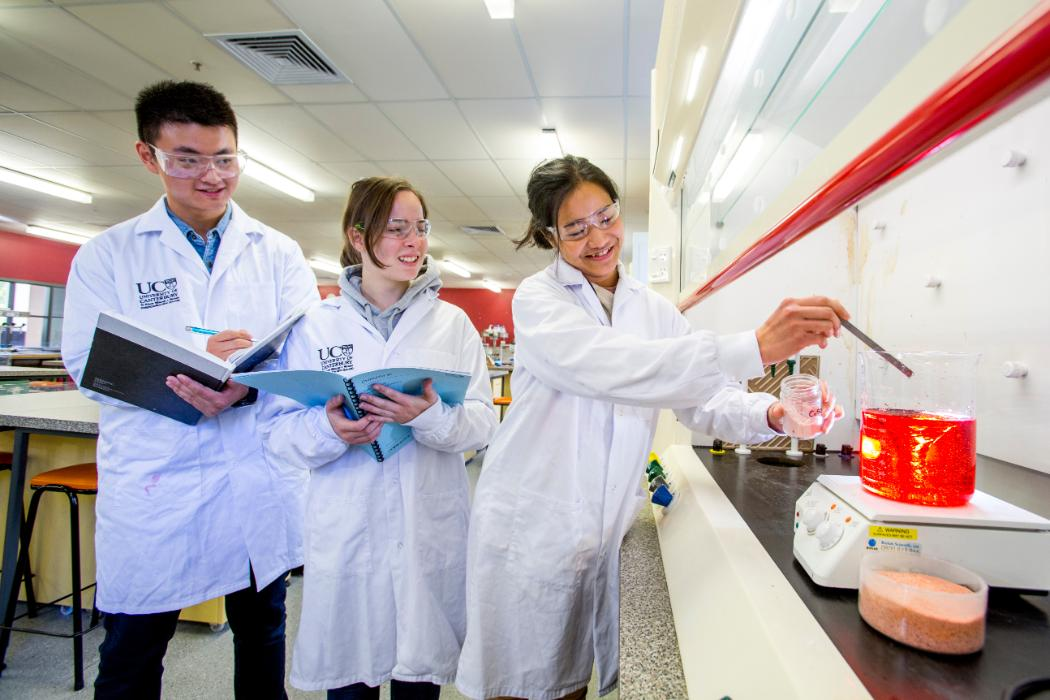 chemistry students with red liquid