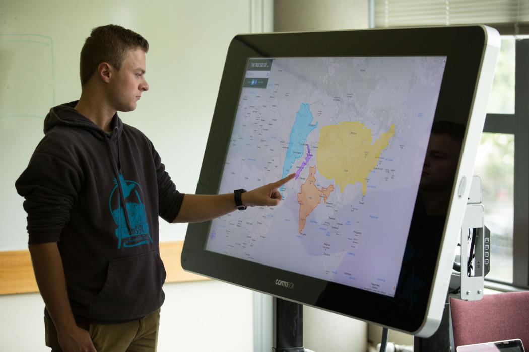 student using large screen and maps
