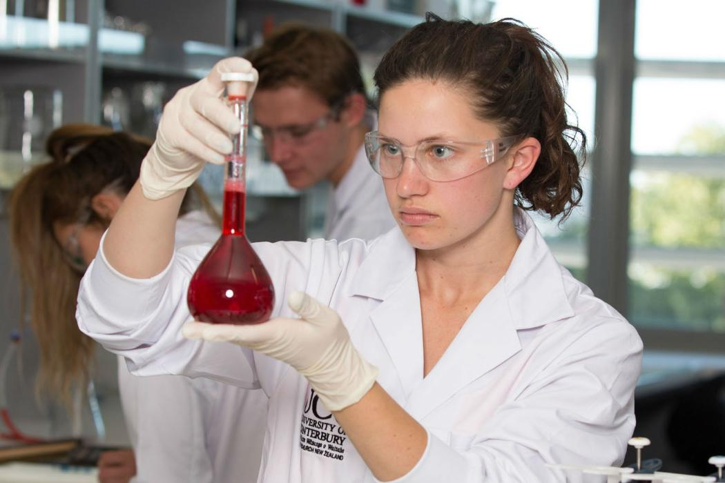 chemistry student in lab with red liquid in flask
