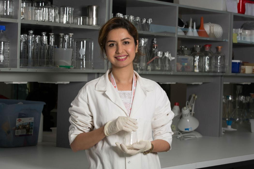 chemistry student in lab wearing white coat