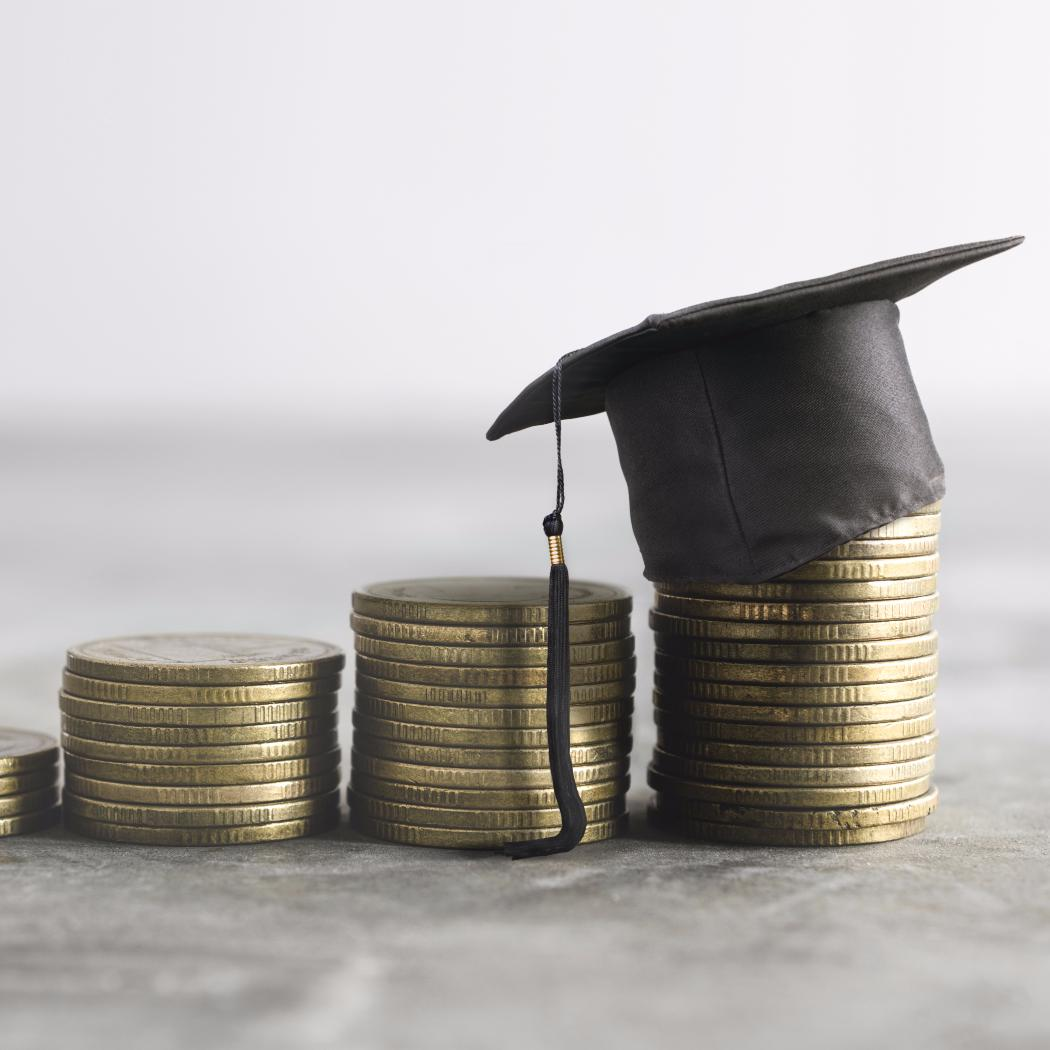 Graduation hat on piles of coins© Shutterstock