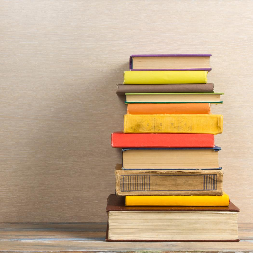 Stack of books against plain wood background