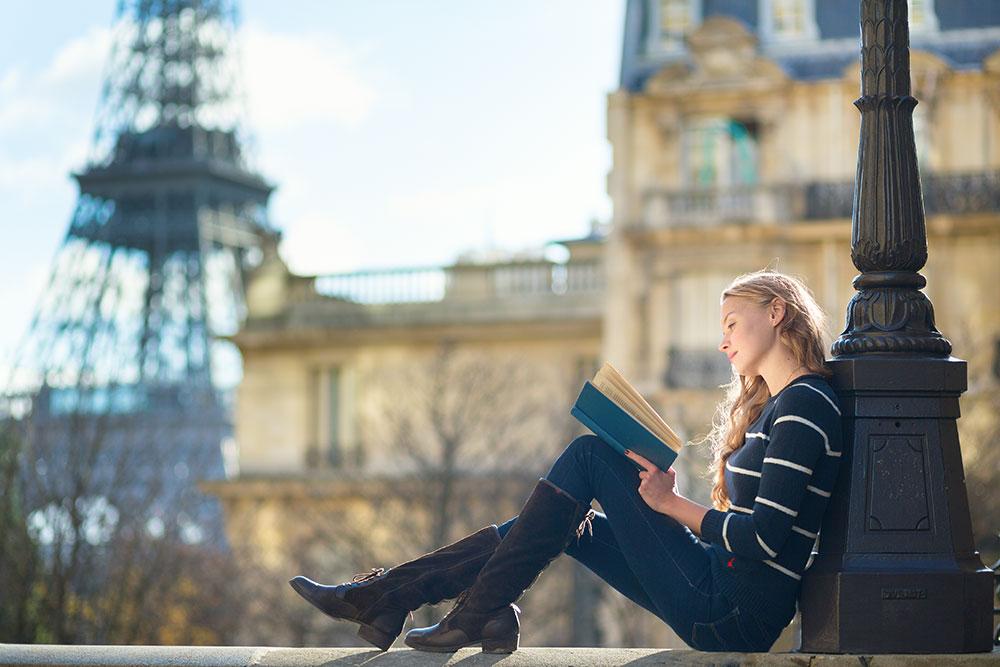 Beautiful young woman in Paris, reading a book Depositphotos 34692223