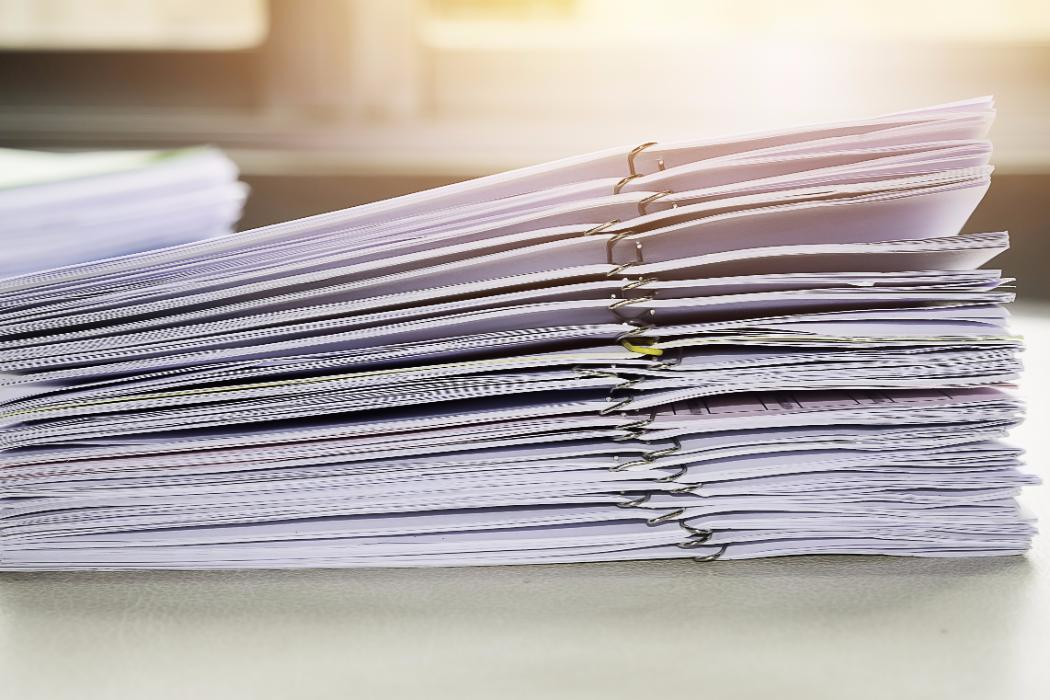 Exam papers stacked on desk