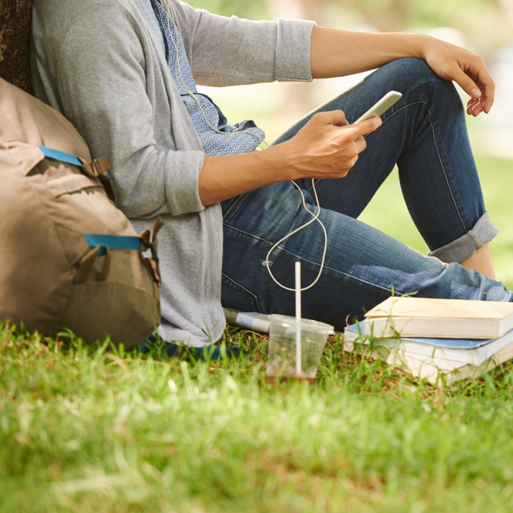 student leans against tree while texting
