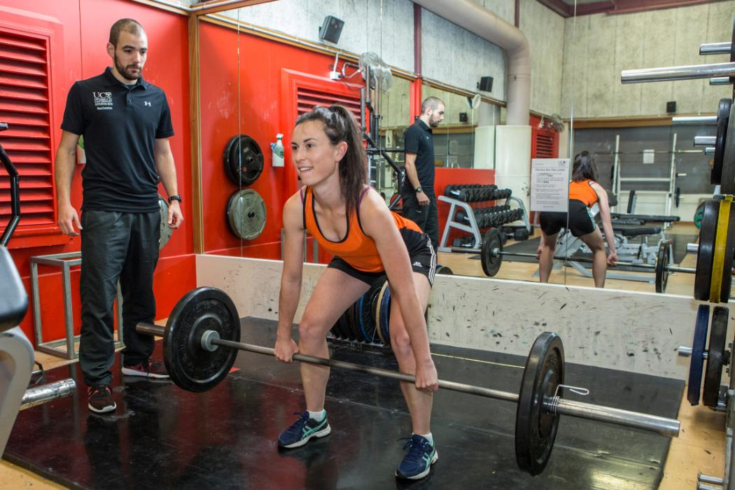 Female deadlifting with trainer