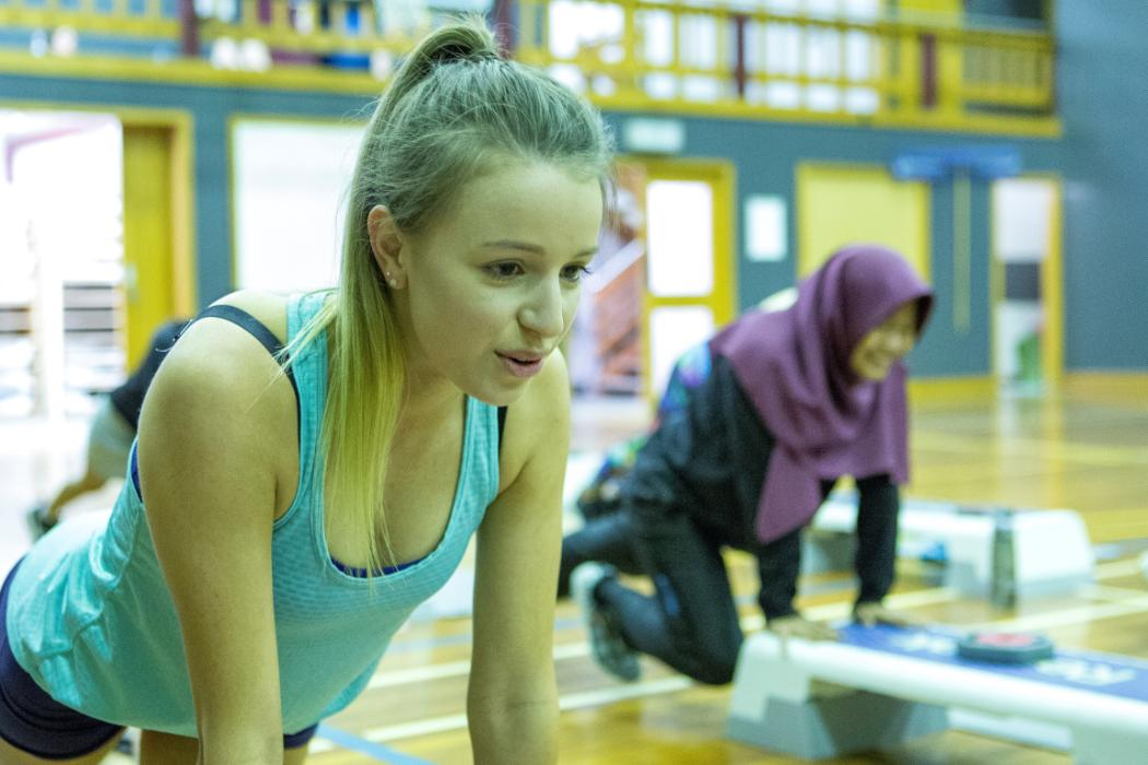 Two students doing mountain climbers on steps in gymnasium