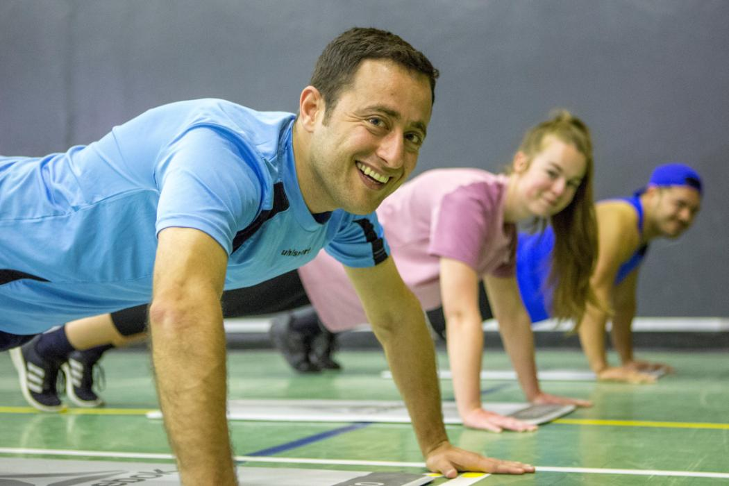 3 people doing press-ups in sportshall HIIT class