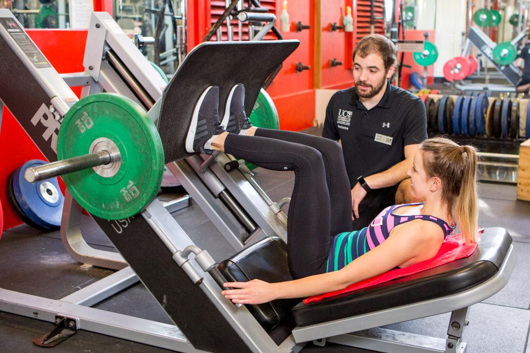 Instructor helping with Leg Press - UC Rec Centre