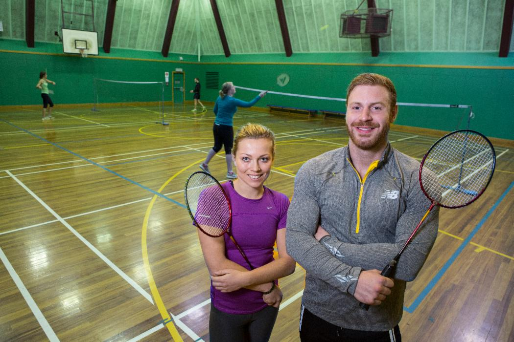 two students badminton looking at camera