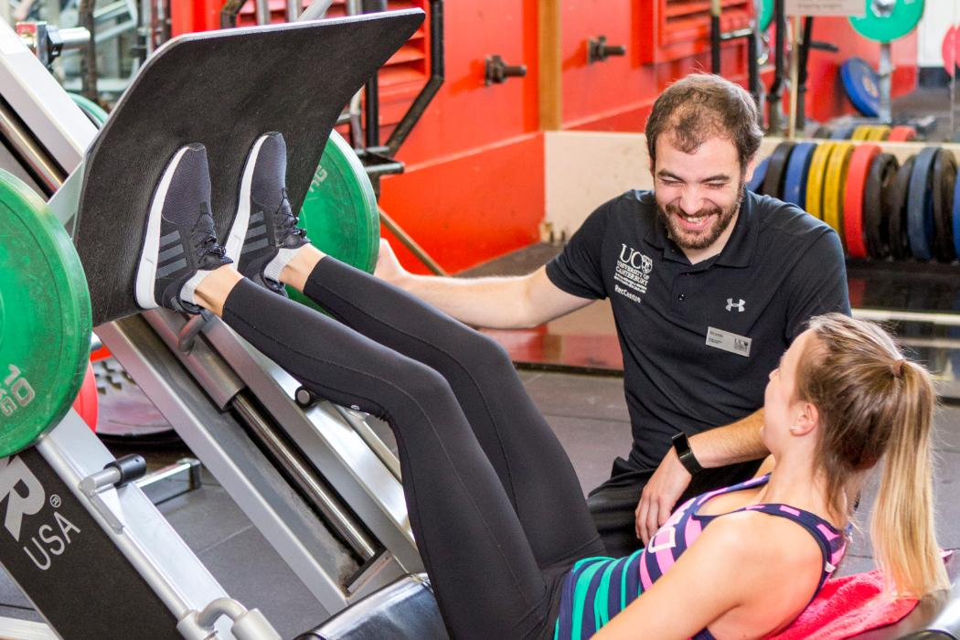 girl on leg press with trainer