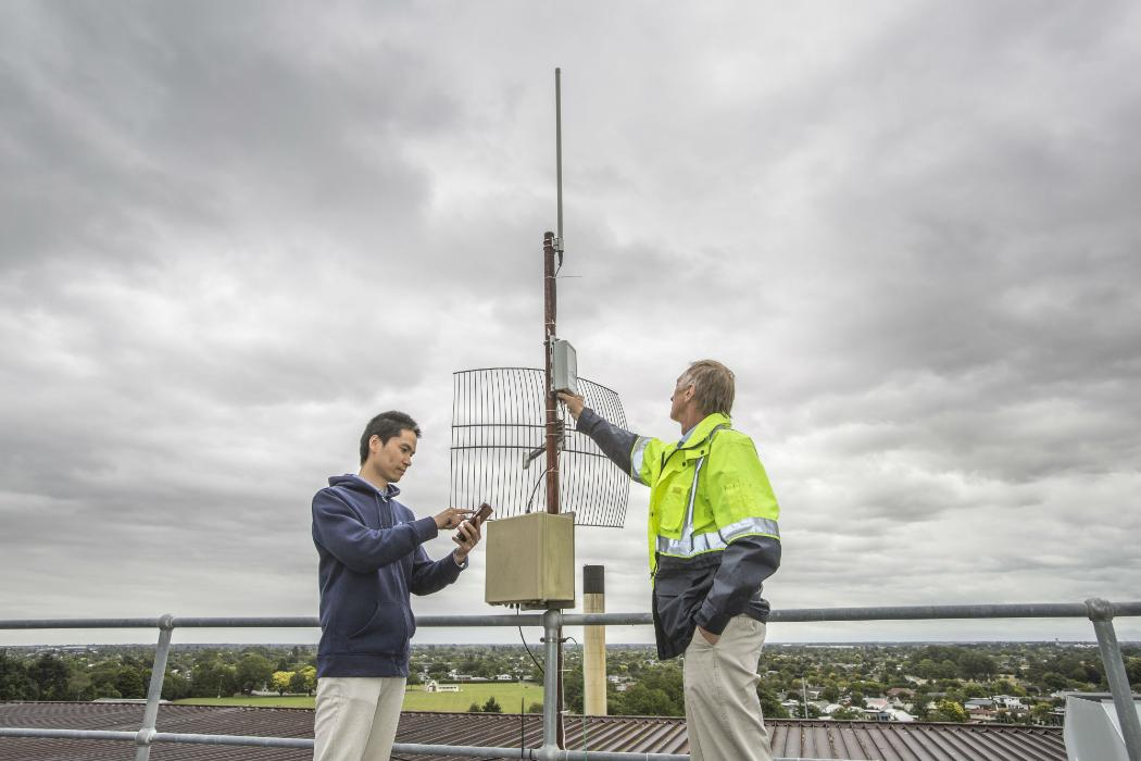 Two researchers testing an antenna on building